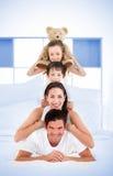 Die lächelnde Familie, die auf jeden anderen sich lehnt, schultert in Bett Lizenzfreies Stockfoto
