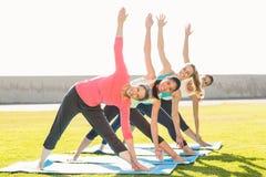 Die lächelnden sportlichen Frauen, die Dreieck tun, werfen in der Yogaklasse auf Stockbilder