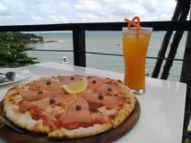 Die Lebensmittelpizza und der Orangensaft essen auf einer weißen Tabelle mit schöner Seelandschaft zu Mittag Lizenzfreie Stockbilder