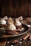 Die Lebkuchenkleinen kuchen, die mit Zimt und Weihnachtsplätzchen und -schneeflocke verziert werden, besprüht lizenzfreie stockfotos