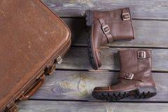 Die Lederstiefel und der alte Retro- Koffer der Männer Stockbilder