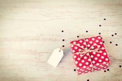 Die leere Anmerkung, die über einem Rot gebunden wurde, punktierte Geschenkbox Hölzerner Hintergrund Abbildung der roten Lilie Stockfoto