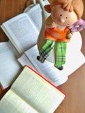 Die Lehmpuppe sitzt auf der Lampe Viele offenen Bücher auf einem Holztisch stockfoto