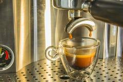 Die letzten Tropfen des starken Espressokaffees, der von einem espr gezeichnet wird Stockbild