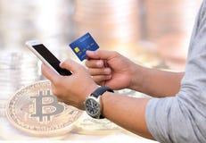 Die Leute übergeben das Halten einer Kreditkarte und die Anwendung des intelligenten Telefons für stockfotografie