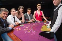 Die Leute, die am Blackjack sitzen, verlegen das Lächeln am Kasino Stockfotografie