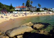 Die Leute, die das warme Wetter auf Lager-Bucht genießen, setzen auf den Strand Lizenzfreie Stockbilder