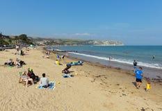 Die Leute, die den Sommersonnenschein Swanage genießen, setzen Dorset England Großbritannien mit Wellen auf dem Ufer auf den Stra Stockbild