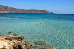 Die Leute, die im klaren blauen Meer von Elafonissi schwimmen, setzen Naturreservat Kreta auf den Strand lizenzfreie stockbilder