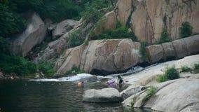 Die Leute, die im See mit Flößen schwimmen, geben, die Ströme Auftrieb, die in den See fließen und beruhen auf Schloss-Spitze stock video