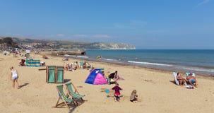 Die Leute, die im Sommersonnenschein Swanage sich entspannen, setzen Dorset England Großbritannien mit Wellen auf dem Ufer auf de Stockfotos
