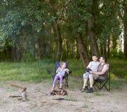 Die Leute, die im Wald, Familie Active in der Natur kampieren, zünden Feuer, Sommersaison an Lizenzfreie Stockbilder