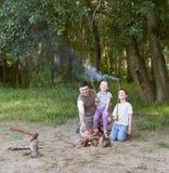 Die Leute, die im Wald, Familie Active in der Natur kampieren, zünden Feuer, Sommersaison an Stockfoto