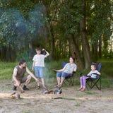 Die Leute, die im Wald, Familie Active in der Natur kampieren, zünden Feuer, Sommersaison an Lizenzfreies Stockfoto