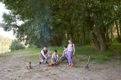 Die Leute, die im Wald, Familie Active in der Natur kampieren, zünden Feuer, Sommersaison an Stockbild