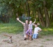 Die Leute, die im Wald, Familie Active in der Natur kampieren, zünden Feuer, Sommersaison an Lizenzfreie Stockfotos
