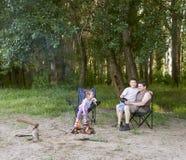 Die Leute, die im Wald, Familie Active in der Natur kampieren, zünden Feuer, Sommersaison an Lizenzfreies Stockbild