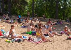 Die Leute, die in Moskva-Fluss ein Sonnenbad nehmen, setzen bei Serebryany Bor auf den Strand Lizenzfreies Stockbild