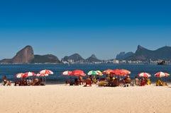 Die Leute, die in Niteroi sich entspannen, setzen mit Ansicht zu Rio de Janeiro auf den Strand Lizenzfreie Stockfotografie