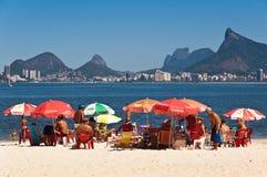 Die Leute, die in Niteroi sich entspannen, setzen mit Ansicht zu Rio de Janeiro auf den Strand Stockbild