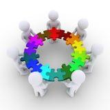 Die Leute, die Puzzlespielstücke halten, schlossen in einem Kreis an Stockbild