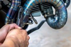 Die Leute, die Hand halten, reparieren ein Motorrad benutzen einen Schlüssel stockfoto