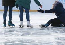 Die Leute helfen, nach einem Fall aufzustehen eislaufend auf die Eisbahn Stockbilder