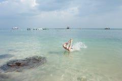 Die Leute springend in das Meer, gegen Hintergrund von Yachten, von Motorbooten und von Rollern lizenzfreie stockbilder