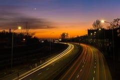 Die Lichter von Autos auf der Straße während des Sonnenuntergangs Lange Berührung Lizenzfreie Stockfotos