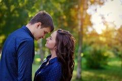 Die liebevollen jungen Jugendpaare, die mit Augen umarmen, schlossen draußen Stockbilder