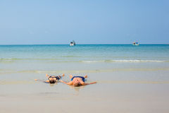 Die Liebhaber, die im landwash auf einer Prämie liegen, setzen auf den Strand Stockfotografie