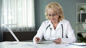 Die on-line-Krankenblätter des weiblichen Arzt- für Allgemeinmedizinlesepatienten auf Tablette stockfotos