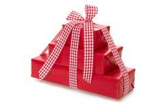 Die lokalisierten Geschenke, die im roten Papier mit einem Rot eingewickelt wurden, überprüften Band Lizenzfreie Stockfotos