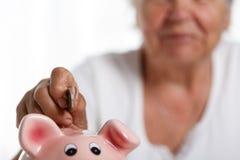 Die ältere Frau, die Stiftgeld steckt, prägt in rosa piggybank Schlitz Lizenzfreie Stockfotos