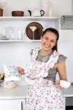 Die lustige nette Hausfrau in der Küche bereitet Tee zu Lizenzfreie Stockbilder