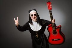 Die lustige Nonne mit dem roten Gitarrenspielen Lizenzfreie Stockbilder