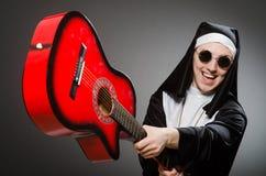 Die lustige Nonne mit dem roten Gitarrenspielen Lizenzfreie Stockfotografie