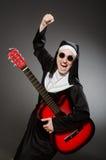 Die lustige Nonne mit dem roten Gitarrenspielen Stockfotos