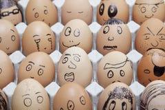Die lustigen Gesichter, die an auf braunen Eiern gemalt wurden, vereinbarten im Karton Stockbilder