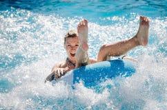 Die lustigen Paare, die ein schnelles Wasser nehmen, fahren auf ein Flossspritzwasser Reisenkoffer mit Meerblick nach innen stockbilder