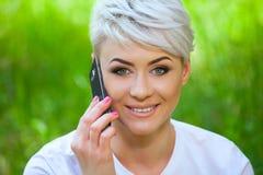 Die Mädchen-blonde Unterhaltung an einem Handy Stockfoto