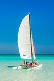Die Mädchen, die auf ein buntes Katamaran in Varadero segeln, setzen in Kuba auf den Strand Lizenzfreie Stockfotos