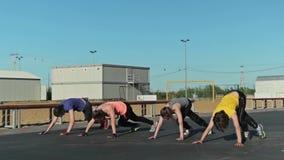 Die Mädchen, die burpee tun, trainieren und eine andere Übung stock footage