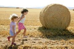 Die Mädchen, die mit dem runden Weizen spielen, trockneten Ballen Lizenzfreies Stockbild