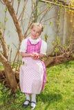 Die Mädchen im Dirndl sitzen im Garten und in den Spielen lachend mit Ostereiern Stockfoto