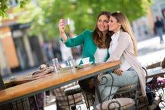 Die Mädchen nehmen selfie und das Lachen lizenzfreie stockfotografie