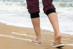 Die Mädchen ` s Beine, die auf den Strand gehen stockfotografie