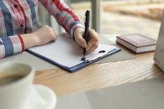 Die Mädchen ` s Hand schreibt in schwarzen Stift auf ein weißes Blatt Papier Lizenzfreie Stockfotos
