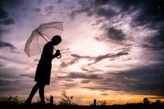 Die Mädchen silhouettieren gehendes alleinim freien und Regenschirm der Art herein Stockfotografie