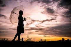 Die Mädchen silhouettieren gehendes alleinim freien und Regenschirm der Art herein Stockbilder